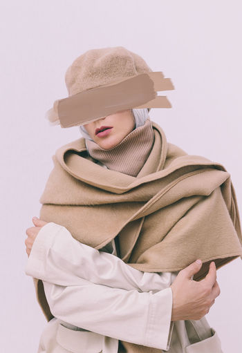 Woman in warm clothing against white background