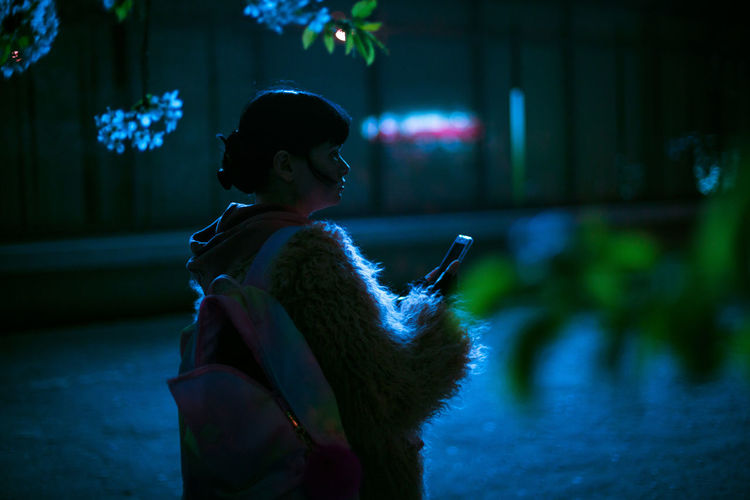 Woman holding phone while standing outdoors at night