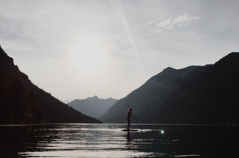 Woman on paddle board in sea against sky during sunny day