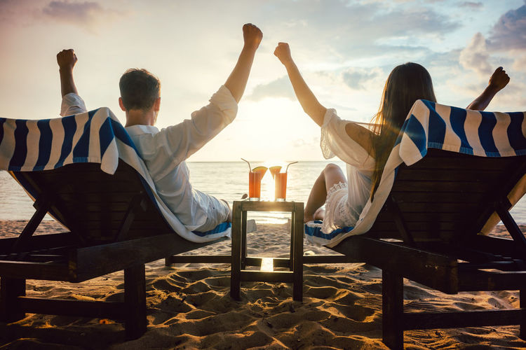 Man and woman enjoying the sunset in their tropical vacation Couple Deck Chair Drinks Freedom Man Tourist Woman Beach Hotel Ocean Outdoors People Relaxation Resort Sea Sitting Sky Sunset Vacation Water