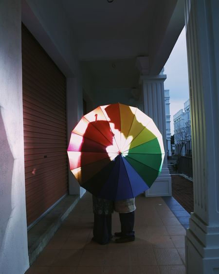 Couple standing with umbrella in building