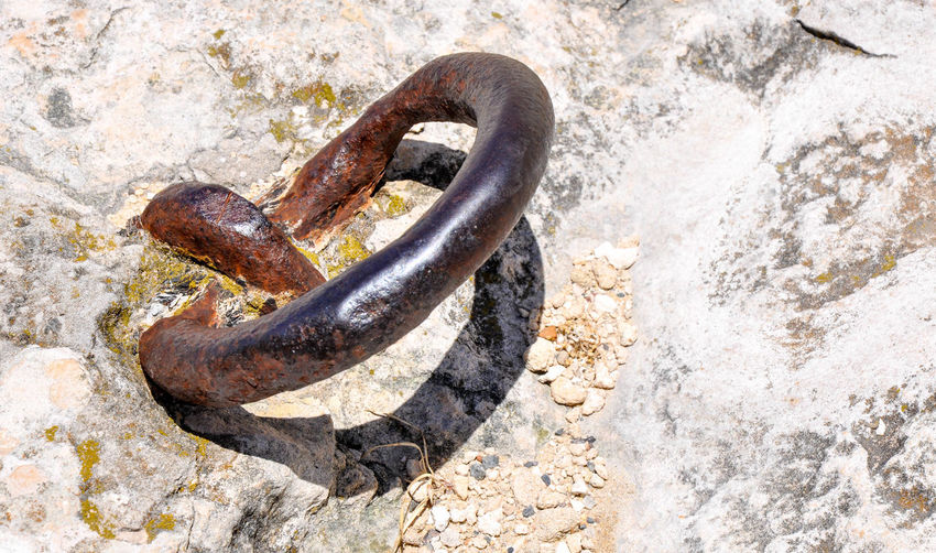 Close-up of rusty metal mounted on rock