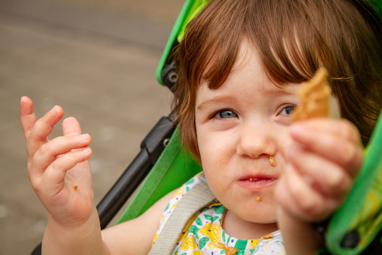 Close-up portrait of baby girl holding food on carriage