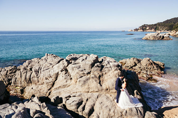 High Angle View Of Newlywed Couple Romancing At Beach Against Clear Sky During Sunny Day