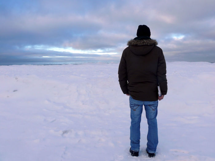 Full length rear view of man standing on snow covered field against cloudy sky