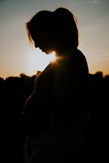 Silhouette of pregnant woman standing against sky during sunset