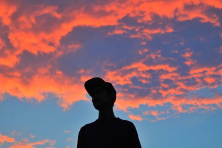 Rear view of silhouette man standing against orange sky