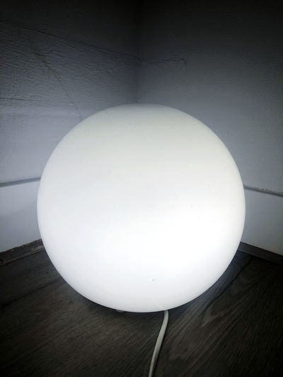 Close-up of illuminated light bulb on wall at home
