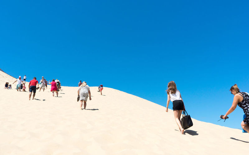 People walking on sand at beach against clear blue sky