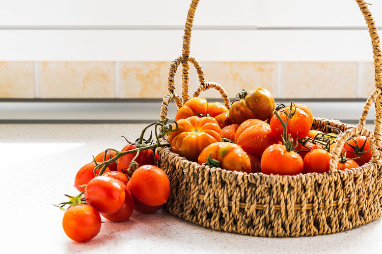 bunches of tomatoes arranged in a basket in the late summer sunshine Diet Dinner Lunch Meal Stack Basket Bunch Food And Drink Freshness Harvest Healthy Eating Indoors  Ingredient Italian Food Juicy Kitchen No People Nutrition Organic Raw Food Red Color Ripe Still Life Tomato Vegetable