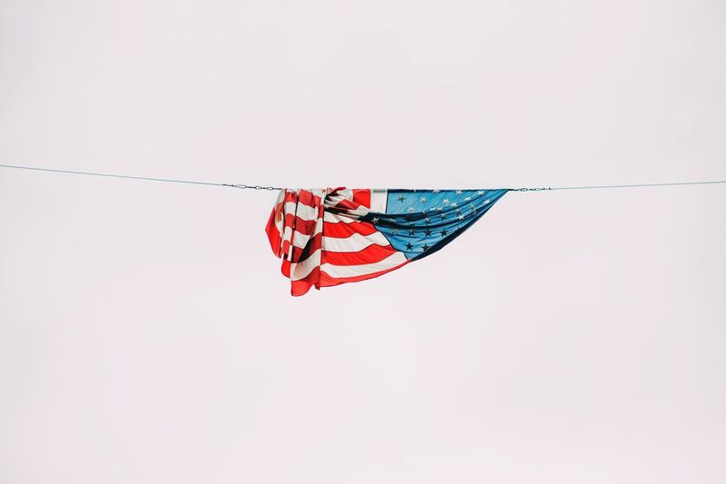 Low Angle View Of American Flag Hanging From Rope Against Clear Sky