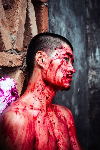 Young Man Looking Away With Blood On Body While Leaning On Wall