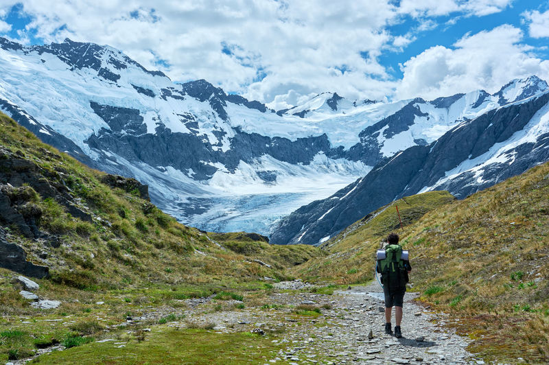Rear view of man walking on dirt road against snowcapped mountains