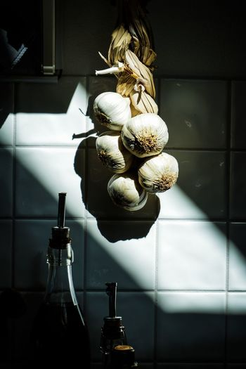 Close-up of garlic hanging on wall at home