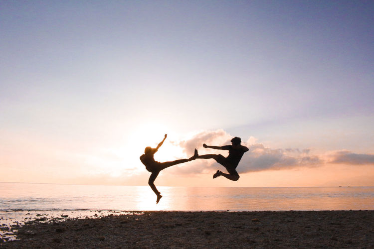 Beach Sky Sea Water Land Nature Full Length Two People Silhouette Togetherness Positive Emotion Jumping Emotion Sunset Men Horizon Over Water Horizon Mid-air People Freedom