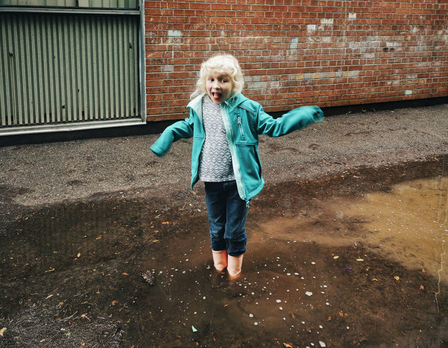 Full length portrait of boy standing against brick wall