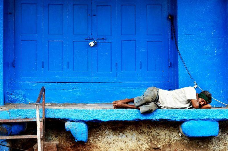 Poor man sleeping against closed shop