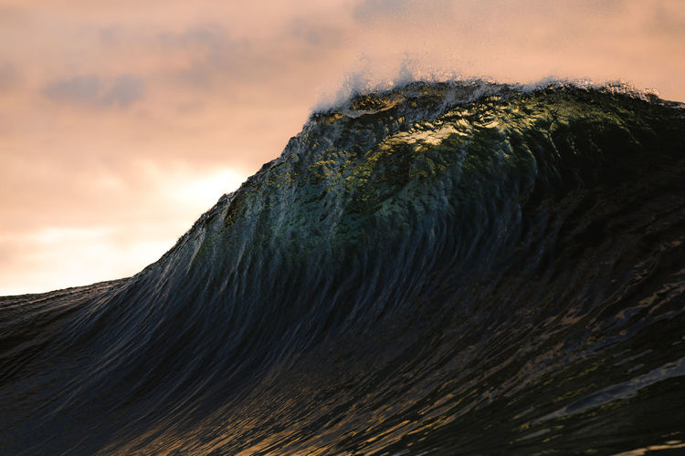 Big wave before crashing under the sunset sky in canary islands