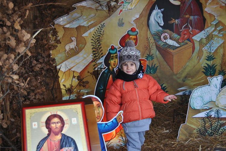Boy wearing warm clothing while playing at nativity scene