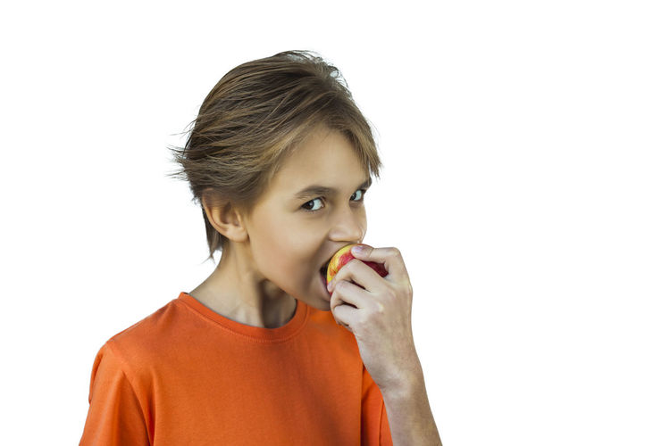Young boy in orange t-shirt eating a red apple Young Boy In Orange T-shirt Eating A Red Apple