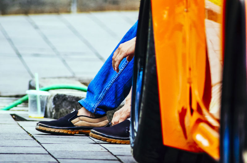 Low Section Of Person Sitting On Footpath
