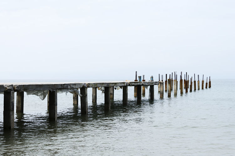 Remains of an Old Pier Water Sea Pier Beauty In Nature Remains Old Pier Deterioration Deteriorated Columns Pillars Abstract Concept Conceptual Destroyed Resistance  Dilapidated Weathered Old Plant Ocean Tranquility Nostalgia Past Rusty Broken