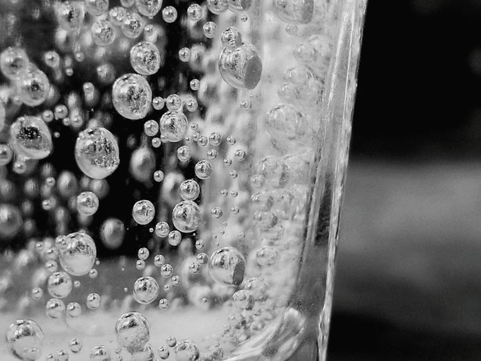 Black and white close-up of bubbles in water in a glass