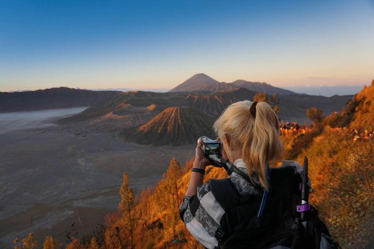 Rear view of woman photographing at bromo-tengger-semeru national park