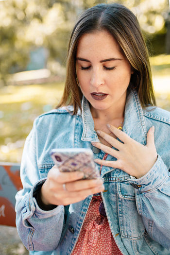 Worried woman using smart phone at park