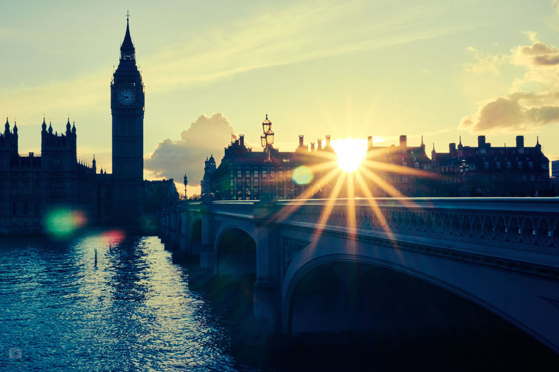 Westminster bridge over thames river by big ben against bright sky at morning
