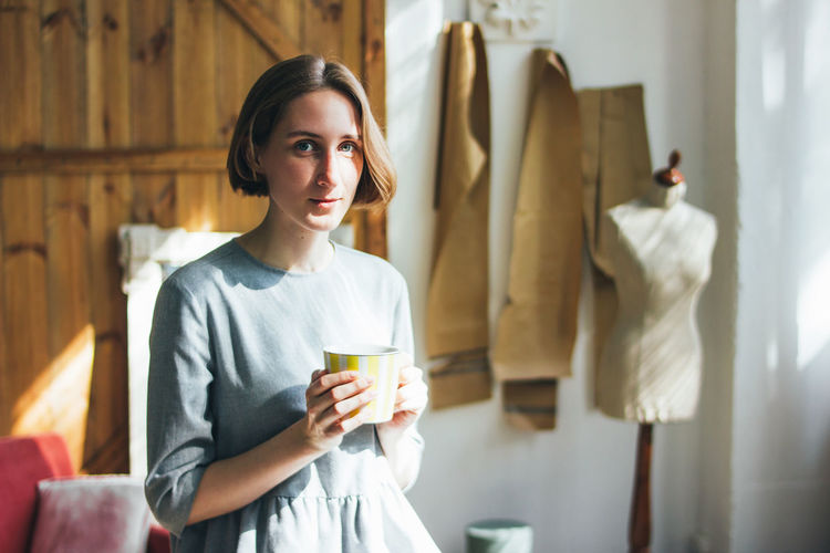 Portrait of young woman drinking coffee while standing against wall