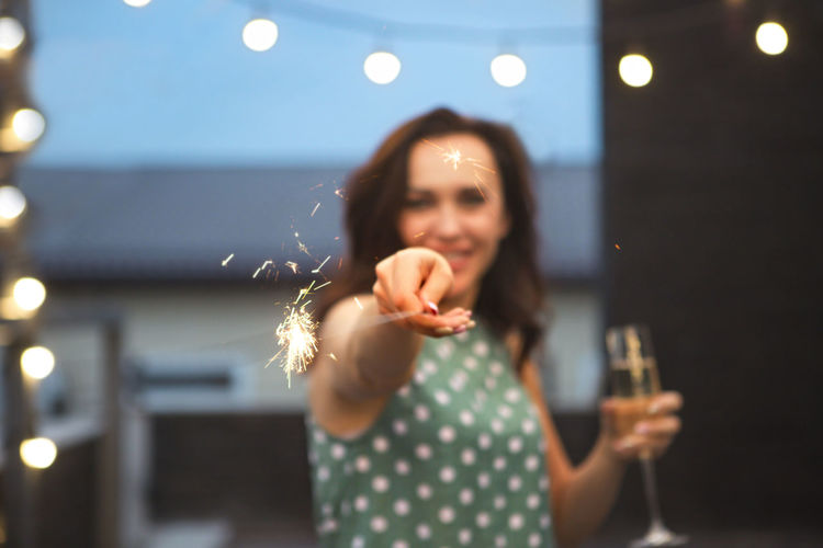Portrait of smiling woman holding sparkler
