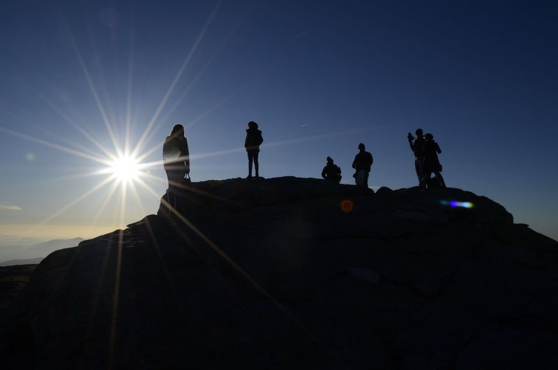 Silhouette People Standing On Mountain Against Sky