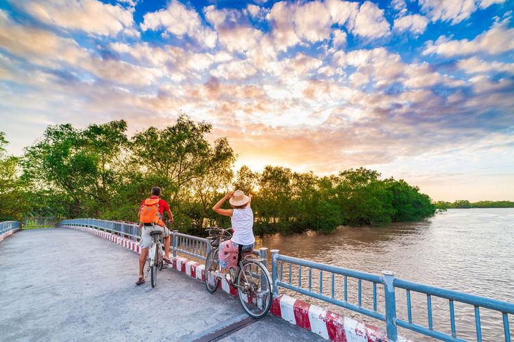 People riding bicycle on riverbank against sky