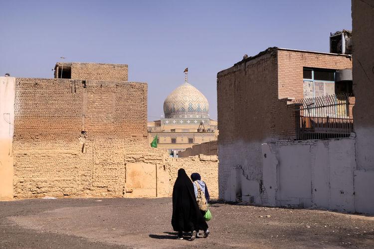 Women walking against buildings