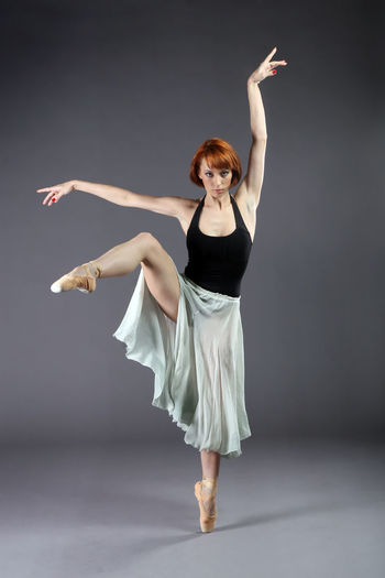Portrait Of Ballet Dancer Dancing Against Gray Background