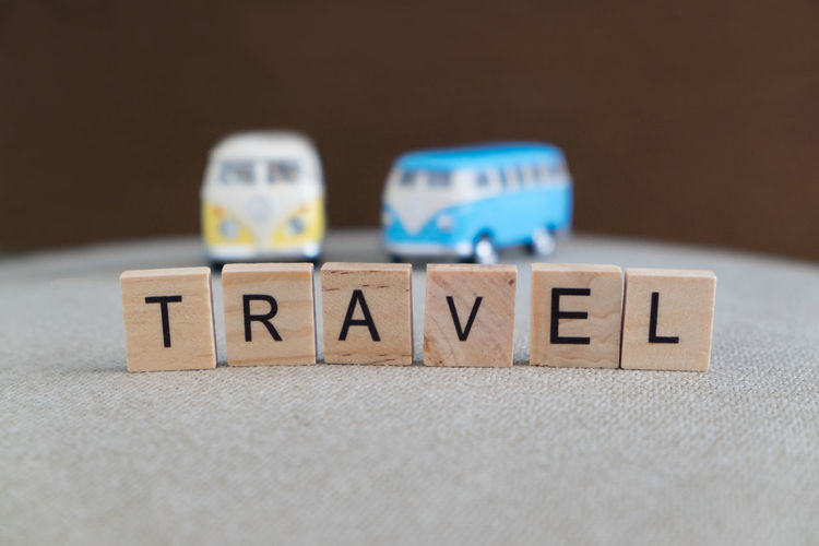 Models Transportation Travel Trip Alphabet Block Blue Blurred Background Capital Letter Close-up Communication Cube Shape Focus On Foreground Indoors  Letter No People Selective Focus Single Word Still Life Table Text Toy Toy Block Western Script Wood - Material