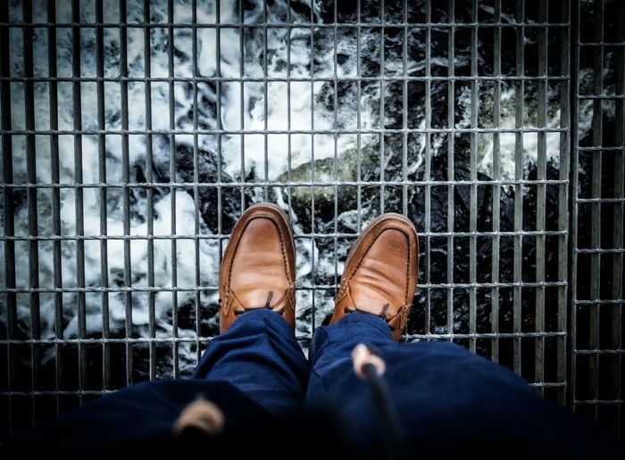 Low section of person standing on metal grate over river