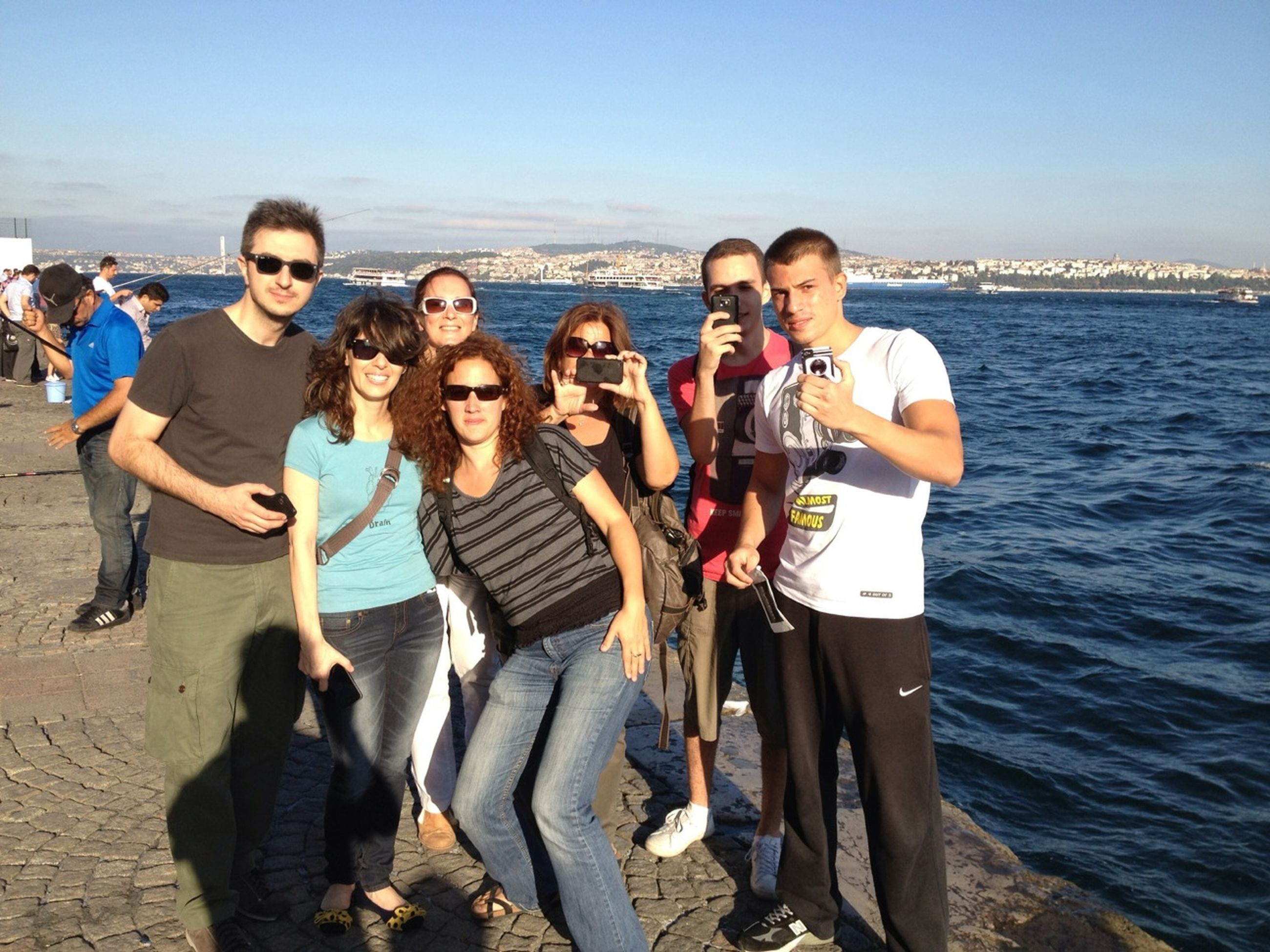 water, lifestyles, togetherness, leisure activity, sea, love, bonding, friendship, casual clothing, vacations, young men, men, enjoyment, large group of people, standing, person, happiness, beach