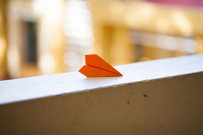 Close-up of paper airplane on retaining wall