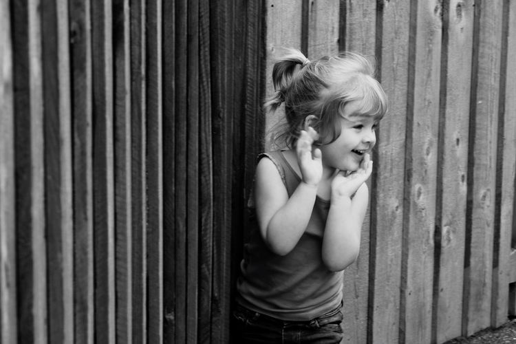 Cute girl with hand on cheek looking away while standing against fence