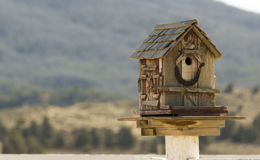 Close-up of wooden birdhouse against mountain