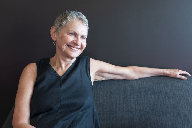 Laughing older woman Smiling Looking At Camera Portrait Studio Shot Gray One Person Indoors  Happiness Front View Adult Gray Hair Senior Adult Waist Up Cheerful Black Background Casual Clothing Confidence  Hairstyle Black Background Woman
