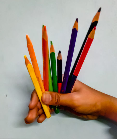 Close-up of hand holding colored pencils against white background