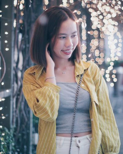 Smiling young woman standing against illuminated defocused lights at night