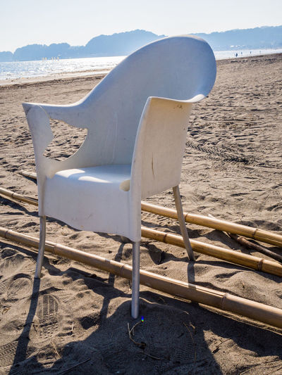 white chair on a beach Bamboo Sticks Beach Chair On A Bea Close-up Empty Loneliness No People Sand Sea Shore Sunlight White Chair On A Beach