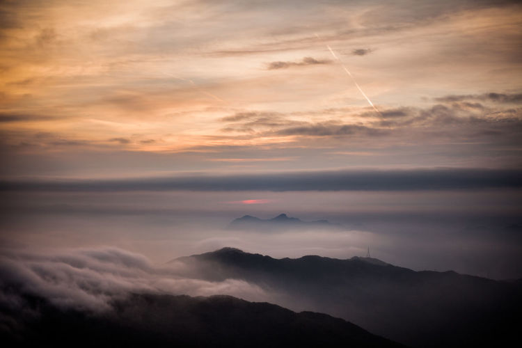 Scenic View Of Cloudscape Covering Mountains Against Sky During Sunset