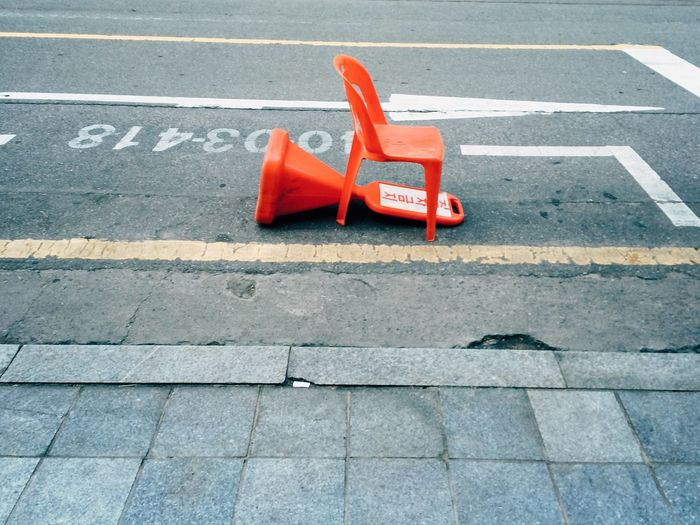 Plastic parking barrier and a chair in the street
