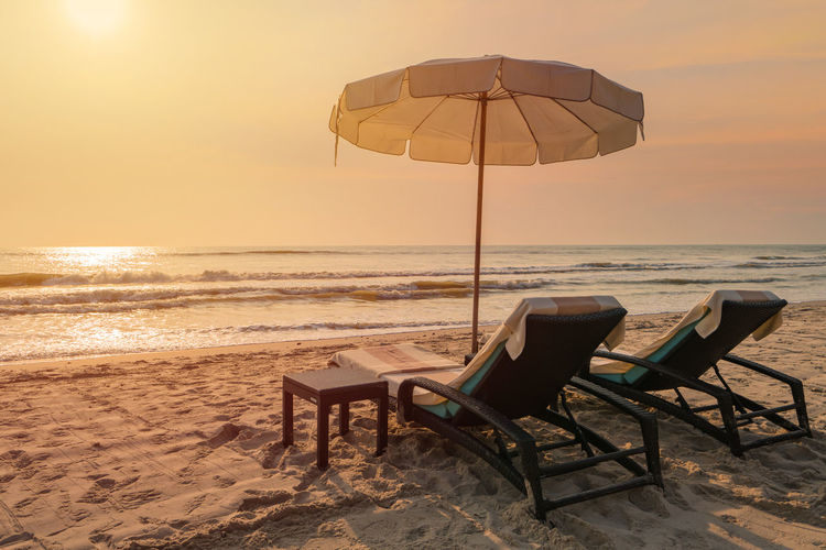 Deck chairs on beach against sky during sunset