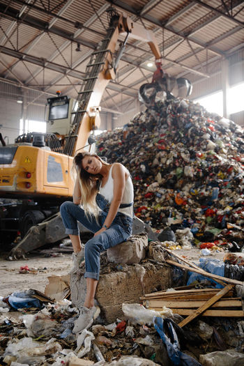 Portrait of young woman against garbage heap